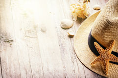 Summer holiday setting with straw hat and seashells Royalty Free Stock Photo