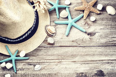 Summer holiday setting with straw hat and seashells. On wooden background royalty free stock images