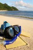 Summer holiday - snorkling. Beach with snorkling equipment and island in the background stock photography
