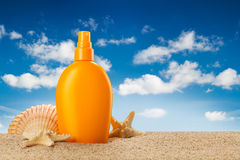 Summer holiday - suntan oil on beach Stock Photos