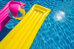 Summer holiday at swimming pool. Summer holiday background concept, relaxing in swimming pool, air beds and inflatable ball on blue pool water Stock Photo
