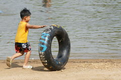 Boy rolling a tire on the beach Stock Photography