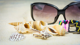Summer holiday theme with sea shells, sunglasses and swimsuit with ethnic ornament on sandy beach Royalty Free Stock Images
