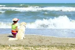 Young Little Girl And Golden Retriever Dog Sitting On The Beach. Summer Holiday, Travel, Happiness, Pets Concept. Young Girl Playing With A Dog On The Beach Stock Photo