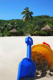 Summer holiday - tropical island. Summer holiday concept with bucket and spade, resort huts in the background royalty free stock photos