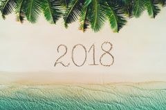 Summer holiday on tropical island. 2018 write on beach sand. Pal. M trees and sea waves Royalty Free Stock Photography