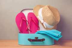 Summer holiday vacation concept with decorative suitcase and flip flops. Stock Image