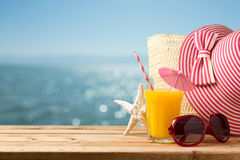 Summer holiday vacation concept with orange juice, hat and sunglasses over sea beach royalty free stock photos