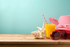 Summer holiday vacation concept with orange juice, sunglasses and seashells. On wooden table royalty free stock photography