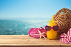 Summer holiday vacation  concept with pineapple juice, beach fashion bag and flip flops on wooden table over sea beach background. Summer holiday vacation stock photos
