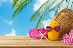 Summer holiday vacation concept with pineapple juice, beach fashion bag and flip flops on wooden table over sea beach background. Summer  holiday vacation royalty free stock images