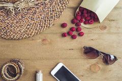 Summer holiday, vacation, relaxation concept. Raspberries, straw. Hat, mobile phone, smartphone, headphones, sunglasses from above, top view, flat lay on wooden Stock Images