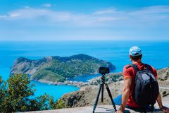 Summer holiday weekend visiting Greece Europe. Male freelance photographer with backpack enjoying capture time lapse of. Mediterranean village Assos from top Stock Images