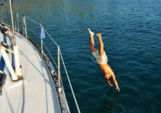 Summer Holiday On A Yacht. A boy jumping from a yacht in the sea Stock Photos