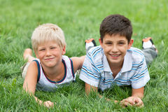 Summer holidays. Two friendly handsome boys are lying on the grass Royalty Free Stock Photos