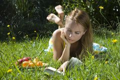 Summer holidays. Young blonde woman reading a book on the grass with plate of fruits on summer holidays royalty free stock photo