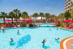Summer holidays in Abu Dhabi, UAE. ABU DHABI, UAE - MARCH 28: People resting at the pool area of Khalidiya Palace by Rotana on March 28, 2014, UAE. Rotana Hotel Stock Photography