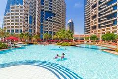 Summer holidays in Abu Dhabi, UAE. ABU DHABI, UAE - MARCH 28: People resting at the pool area of Khalidiya Palace by Rotana on March 28, 2014, UAE. Rotana Hotel Stock Image