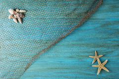 Summer holidays background with a space for advertising. Summer holidays background in blue with fishing net ans seashells and a space for advertising stock images