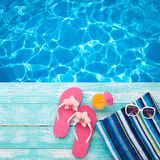 Summer Holidays in Beach Seashore. Fashion accessories summer flip flops, hat, sunglasses on bright turquoise board near the pool. Summer Holidays in Beach Royalty Free Stock Photo