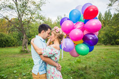 Summer holidays, celebration and dating concept - couple with colorful balloons in nature.  royalty free stock photography