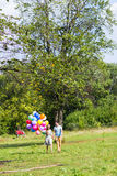 Summer holidays, celebration and dating concept - couple with colorful balloons in nature Royalty Free Stock Photo