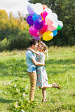 Summer holidays, celebration and dating concept - couple with colorful balloons in nature Stock Photo