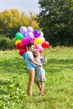 Summer holidays, celebration and dating concept - couple with colorful balloons in nature Stock Image