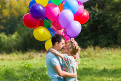 Summer holidays, celebration and dating concept - couple with colorful balloons in nature Stock Photography