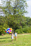 Summer holidays, celebration and dating concept - couple with colorful balloons in nature Stock Images