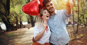 Summer holidays, celebration and dating concept - happy couple. With colorful balloons stock photo