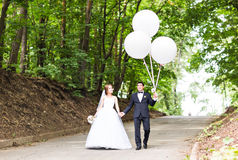 Summer holidays, celebration and wedding concept - couple with colorful balloons. And engagement ring stock photography