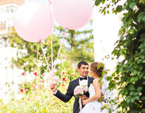 Summer holidays, celebration and wedding concept - couple with colorful balloons. And engagement ring royalty free stock image