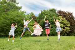 Happy kids jumping in summer park stock image