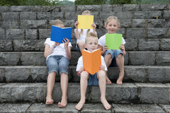 Summer holidays: children with a book seated outdoors on stairs Stock Images