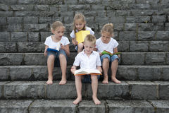 Summer holidays: children with a book seated outdoors on stairs Royalty Free Stock Photos