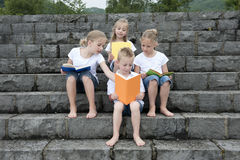 Summer holidays: children with a book seated outdoors on stairs Royalty Free Stock Images