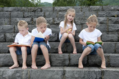 Summer holidays: children with a book seated outdoors on stairs Stock Photos