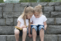 Summer holidays: children with a book seated outdoors on stairs Stock Image