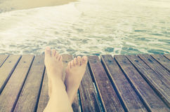 Summer holidays concept background with legs over wooden pier Stock Photos