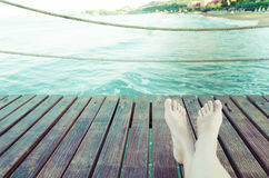 Summer holidays concept background with legs over wooden planks Royalty Free Stock Image