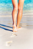 Summer holidays concept. Closeup photo of a sexy womans legs, slim female walking on the beach, carefree lifestyle, summer vacation background, relaxation and Royalty Free Stock Photo