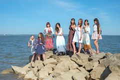 Summer holidays concept - group of smiling young women is resting on the seashore.  Stock Photography