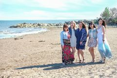 Summer holidays concept - group of smiling young women is resting on the seashore.  Royalty Free Stock Photography