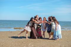 Summer holidays concept - group of smiling young women is resting on the seashore.  Royalty Free Stock Image