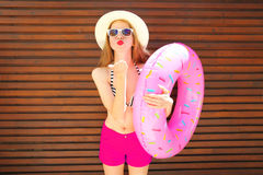 Summer holidays concept - pretty woman with inflatable ring. Sends an air kiss on wooden background Stock Photography