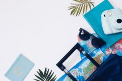 Summer holidays concept.  Travel, tourism and vacation concept background. Traveler accessories. Flat lay. Blue suitcase with trav. Travel bag and straw hat stock images