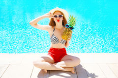 Summer holidays concept - woman with pineapple having fun over a blue water pool Royalty Free Stock Photography