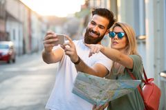 Summer holidays, dating and tourism concept. Smiling happy couple with map in the city. Summer holidays, dating and tourism concept. Smiling couple with map in royalty free stock photography
