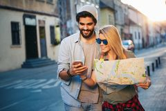Summer holidays, dating and tourism concept. Smiling happy couple with map in the city stock image